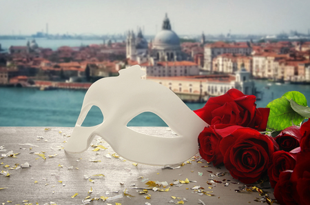 Image of elegant venetian mask and red roses over wooden table in front of blurry Venice background Banco de Imagens