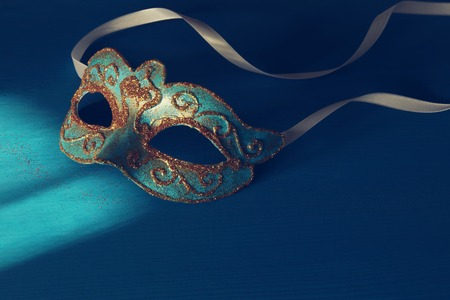 Image of elegant blue and gold venetian, mardi gras mask over blue background Stock Photo