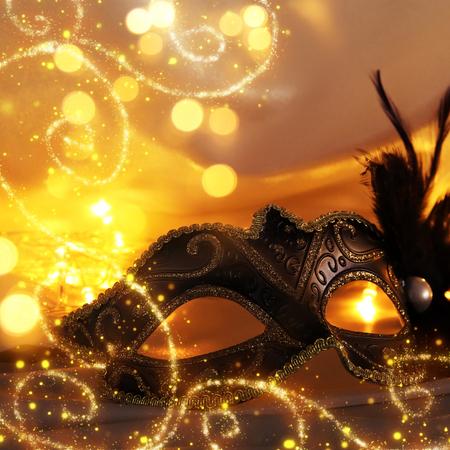 Obraz eleganckiej maski weneckiej na złotym tle jedwabiu