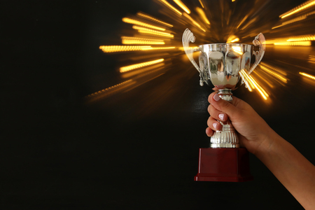 low key image of a woman holding a trophy cup over dark background Stockfoto