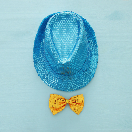 Blue shiny sequined party Hat next to yellow bow over wooden background. Purim celebration concept (jewish carnival holiday). Top view Stock Photo