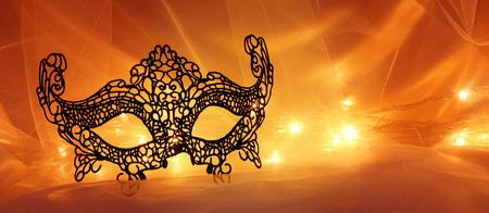 Image of black elegant lace venetian mask over tulle background