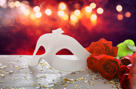 Image of elegant venetian mask and red roses over wooden table.