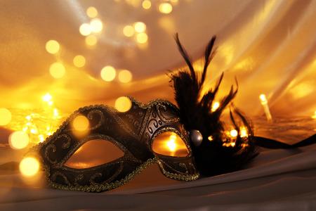 Beeld van elegant Venetiaans masker over gouden zijdeachtergrond