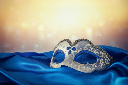 Image of elegant blue and gold venetian mask over blue silk fabric background