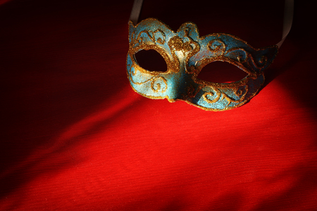 Image of elegant blue and gold venetian mask over red background