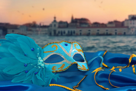 Image of elegant venetian mask on silk fabric in front of blurry Venice background Stock Photo