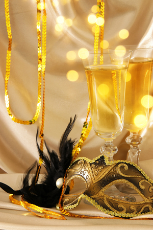 Image of elegant venetian mask and glasses of champagne over gold silk background