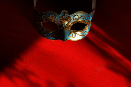 Image of elegant blue and gold venetian, mardi gras mask over red background Stock Photo