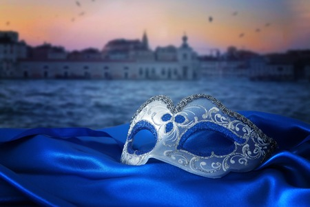 Image of elegant venetian mask on silk fabric in front of blurry Venice background.