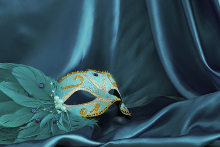 Image of elegant venetian mask over blue silk background
