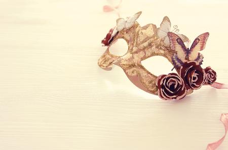Image of delicate elegant venetian mask over wooden white background. Selective focus