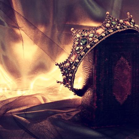 imagen oscura de la corona hermosa de la reina / del rey en el libro viejo. período medieval de fantasía