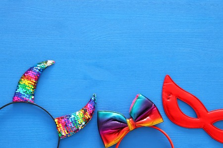 Top view image of carnival masquerade accessories: colorful and funny devil horns, hair bow and red mask over woodeb blue background Фото со стока