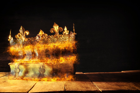 low key of queen/king crown burning over old books. vintage filtered. fantasy medieval period