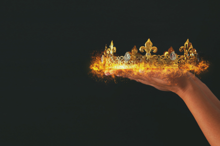 Womans hand holding a burning crown over black background Stock Photo