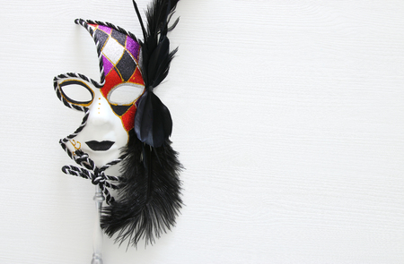 Top view image of dramatic masquerade venetian mask over white background. Flat lay
