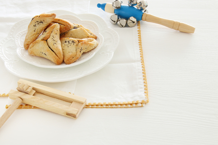 Purim celebration concept (jewish carnival holiday). Traditional hamantaschen cookies over white table