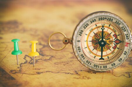 Image of pins attached to map, showing location or travel destination next to vintage compass. selective focus