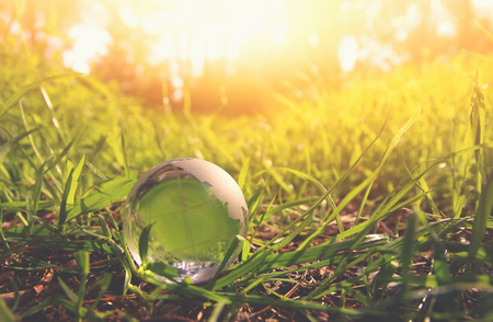 low angle small crystal globe in the grass. travel and global issues concept Standard-Bild