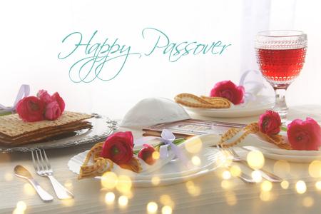페사 축하 개념 (유대인 유월절 휴일 축제 테이블). 히브리어로 된 텍스트가있는 전통 책 : 유월절 학개 (유월절 이야기)