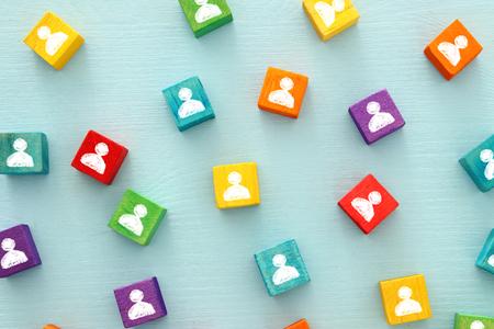 Imagen de bloques coloridos con iconos de personas sobre mesa de madera, recursos humanos y concepto de gestión