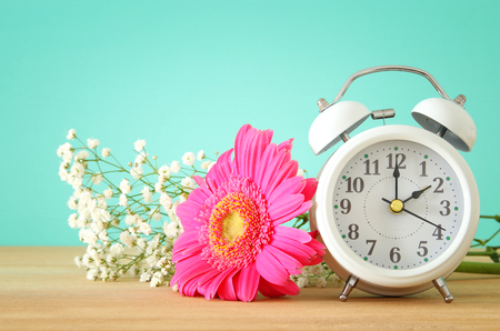 Image of spring Time Change. Summer back concept. Vintage alarm Clock over wooden table Stock Photo - 96042398