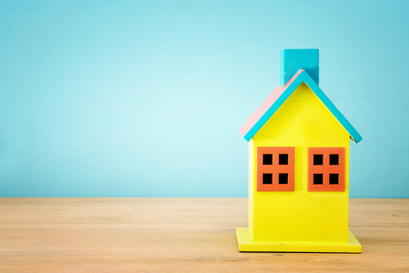 Image of wooden colorful house model over blue background. Real estate concept