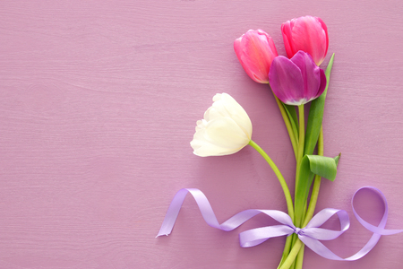 bouquet of pink and white tulips over pastel wooden background. Top view Stock Photo