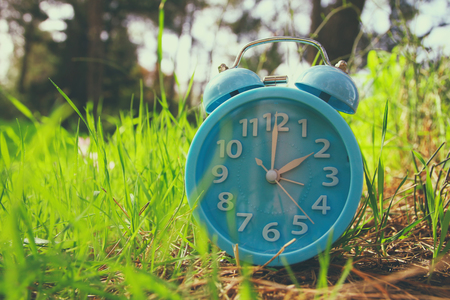 Image of spring Time Change. Summer back concept. Vintage alarm Clock outdoors