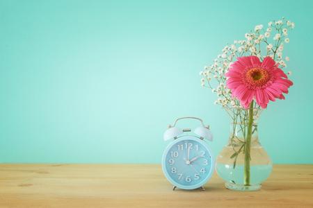 Image of spring Time Change. Summer back concept. Vintage alarm Clock over wooden table