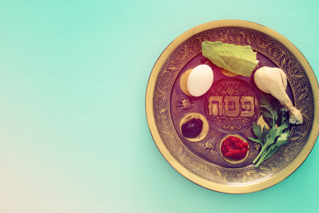 Pesah celebration concept (jewish Passover holiday). Traditional pesah plate with five symbols: horseradish, celery, egg, bone, maror, charoset. Text in hebrew: Passover