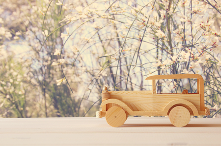 Vintage wooden toy car over wooden table. Nostalgia and simplicity concept