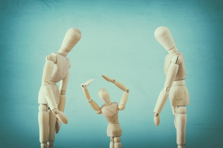 family violence cincept. wooden dummies as parents and child arguing and shouting