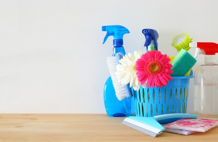 Spring cleaning concept with supplies on wooden table Stock Photo