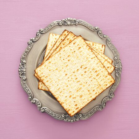 passover background with matzoh over light purple wooden background