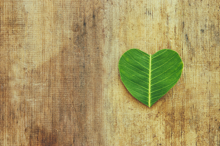 heart shaped leaf over wooden table. ecology and health concept