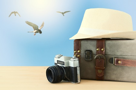 traveler vintage luggage, camera and fedora hat over wooden table infront of blue sky and birds. holiday and vacation concept