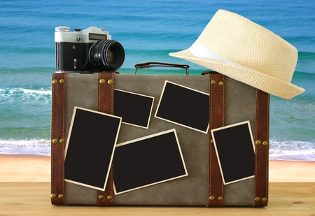 Image of old vintage luggage, fedora hat, vintage old photo camera and blank photos for photography montage mockup over wooden floor.