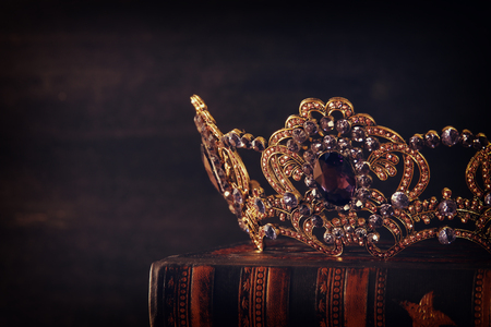 low key image of beautiful queen/king crown over wooden table. vintage filtered. fantasy medieval period Foto de archivo