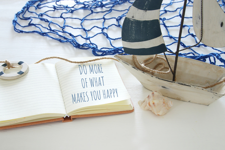 nautical concept image with white decorative sail boat and open notebook: DO MORE OF WHAT MAKES YOU HAPPY Foto de archivo - 98612216