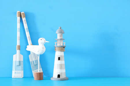 nautical concept with white decorative seagull bird, lighthouse and wooden boat oars over blue background
