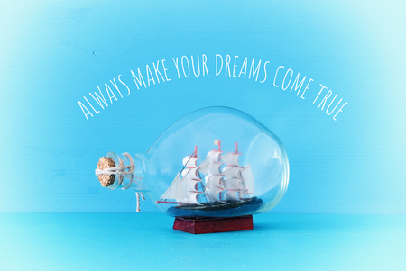 nautical concept image with sail boat in the bottle over blue background with text: Always make your dreams come true