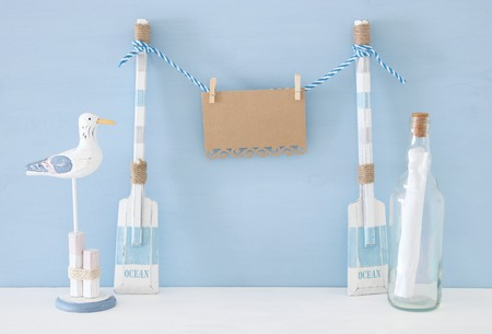 nautical concept with hanging empty note on a string next to letter in the bottle and seagull over blue background