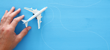 top view photo of mans hand holding toy airplane over blue wooden background Stock Photo