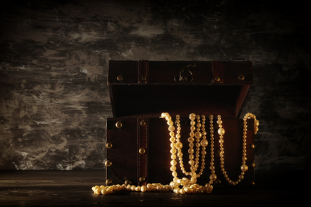 Image of mysterious opened old wooden treasure chest with light. An adventure and fantasy medieval period. Selective focus