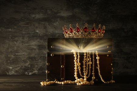 Image of mysterious opened old wooden treasure chest with light and queen/king crown with red Rubies stones. fantasy medieval period. Selective focus.
