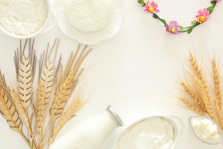 Top view image of dairy products over white wooden background. Symbols of jewish holiday - Shavuot