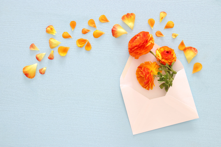 Image of envelope with delicate pastel orange and yellow beautiful flowers arrangement over blue wooden background. Flat lay, top view