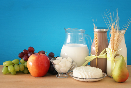 image of dairy products and fruits over wooden background. Symbols of jewish holiday - Shavuot Stock Photo